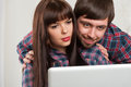 Young couple using laptop at home closeup portrait smiling Stock Photos
