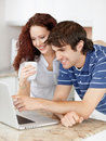 Young couple using a laptop on the kitchen counter Stock Images
