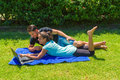Young couple using a laptop lying on grass in the city park lifestyle education and digital communication technology concept Stock Photos
