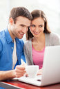 Young couple using laptop smiling Stock Images