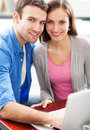 Young couple using laptop smiling Royalty Free Stock Photography