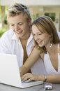 Young couple using laptop smiling attractive sitting at the backyard table and Royalty Free Stock Images