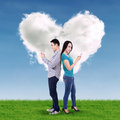 Young couple using mobile phone with heart cloud background Royalty Free Stock Images
