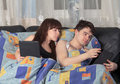 Young couple using tablet PC in their bed Royalty Free Stock Images