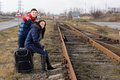 Young couple waiting for a train pointing down the track in excitement as they sit and wait alongside rural railway line with Royalty Free Stock Photography