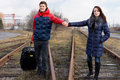 Young couple walking along a railway line holding hands and carrying luggage as they make their way to the station for the start Stock Photos
