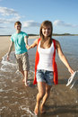 Young Couple Walking Along Shoreline Stock Image