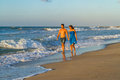 Young couple walking barefoot on a wet beach at happy in jean shorts blue dress along sandy dusk Royalty Free Stock Images