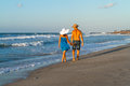 Young couple walking barefoot on a wet beach at happy in jean shorts blue dress wearing hats along sandy dusk Stock Photography
