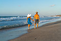 Young couple walking barefoot on a wet beach at happy in jean shorts blue dress wearing hats along sandy dusk Royalty Free Stock Photos