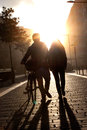 Young couple walking down the street with a bicycle at sunset flare Royalty Free Stock Photos