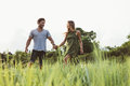 Young couple walking in field of tall grass shot happy the meadow man and women holding hands and together Royalty Free Stock Image