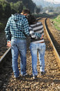 Young couple walking on a railway track Stock Images