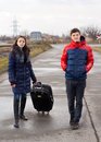 Young couple walking on the road with a suitcase along women pulling behind her alongside rural railway line level Royalty Free Stock Photography
