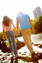 Young couple walking together beside river Stock Photos