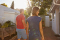 Young couple walking towards their house rear view of in backyard taking walk on a bright sunny day Royalty Free Stock Photos