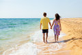 Young couple walks on the beach holding hands and walking Stock Photography