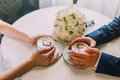 Young couple warming their hands by coffee cups at the table in cafe bouquet of beautiful white flowers on background Royalty Free Stock Image