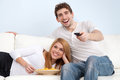 Young couple watching tv at home on a sofa Royalty Free Stock Photo