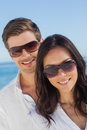 Young couple wearing sunglasses and smiling at camera beach on holidays Royalty Free Stock Photo