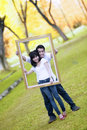 Young couple with wooden frame Royalty Free Stock Image