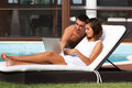 Young couple working near the pool is with a laptop Stock Photos