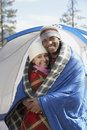 Young couple wrapped in blankets at campsite portrait of a happy multiethnic the Stock Photos