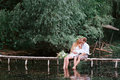 Young couple in a wreath with a bouquet on a wooden bridge laughing lifestyle love romance relationships Stock Photos
