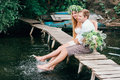 Young couple in a wreath with a bouquet on a wooden bridge laughing lifestyle love romance relationships Royalty Free Stock Image