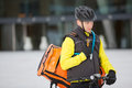Young courier delivery man using walkie talkie male cyclist with bag Stock Image