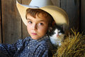 Young cowboy with big brown eyes a and a barn cat blue Stock Images