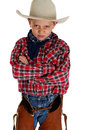 Young cowboy glaring at camera wearing hat and chaps arms folded Royalty Free Stock Photos