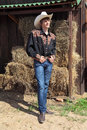 Young cowboy the man in the clothes of a costs about bales of hay Royalty Free Stock Photos