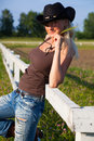 Young cowgirl sitting on a fence Royalty Free Stock Photo