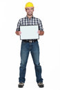 Young craftsman all smiles standing with legs apart holding board Stock Photo