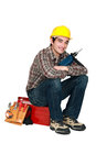 Young craftsman holding drill sitting tool box Stock Photo