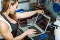 Young craftswoman working using a laptop in the garage Royalty Free Stock Photo