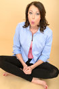 Young Crazy Woman Sitting on the Floor Pulling Silly Expression Royalty Free Stock Photo