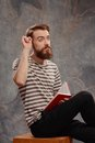 Young creative man posing with notes and creatively independent portrait of bearded tattooed in a striped longsleeve looking up in Stock Image