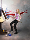 Young creative painter artist blonde woman paint canvas big paintbrush Royalty Free Stock Images