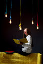 Young creative student with colorful lamps and books Royalty Free Stock Photo