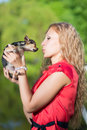 Young curly blond woman kissing little dog Royalty Free Stock Photo