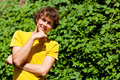 A young curly man in a forest with hair yellow t shirt Royalty Free Stock Photography