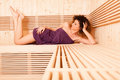 Young curly woman lying on wooden bench with feet up Royalty Free Stock Photo