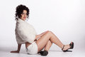 Young curly woman in white fur coat shorts black bra and high heels sitting on the floor Royalty Free Stock Images