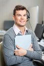 Young customer service representative holding file portrait of male in office Royalty Free Stock Photography