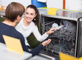 Young customers choosing new dish washing machine in appliance Royalty Free Stock Photo