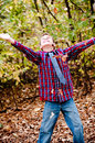 Young cute boy looking up with leaves falling down Stock Photos