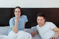 Young cute caucasian couple man and woman in bed smiling men women looking at camera domestic morning atmosphere Royalty Free Stock Photos