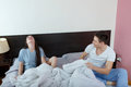 Young cute caucasian couple man and woman in bed smiling men women looking at camera domestic morning atmosphere Stock Photography